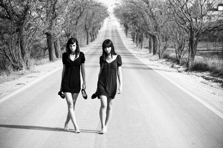 street fashion: Two couple of young models parading in the middle of the road Stock Photo
