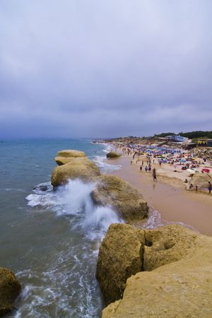 gale: Storm over Algarve Gale beach full of tourists. Stock Photo