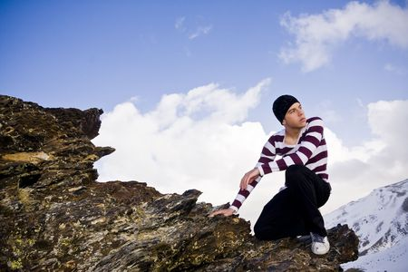 Young man posing at high altitude after climbing a cliff photo