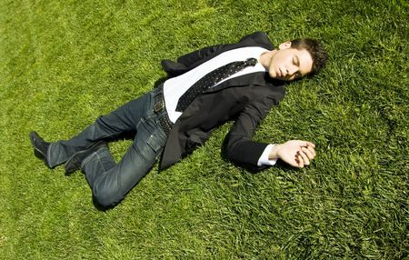 Businessman resting over the grass photo
