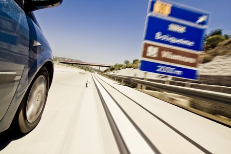 faster: Road signs blurred due the vehicle high speed.