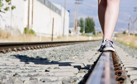buttom: Woman walking in equilibrium over rail track.