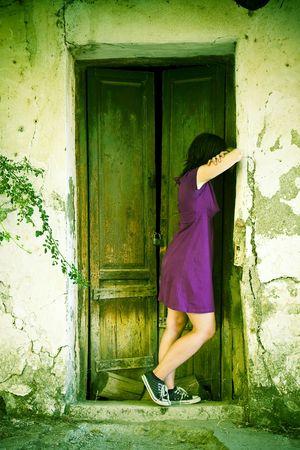Young sad woman facing old cracked wall. photo