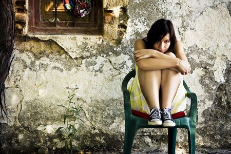 tormented: Young sad woman sited on dirty place.
