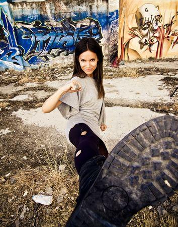 банда: Young rebel woman kicking in dirty urban background. Focus on face. Фото со стока