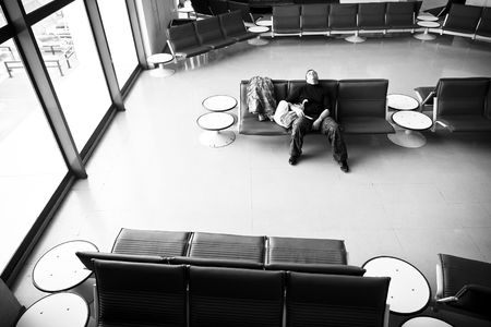 arrivals: Resting man at empty station, black and white tone.