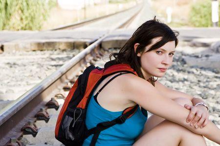 Young backpacker woman sitting near railway. photo