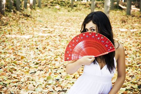 to observer: Beautiful woman in a forest behind red fan