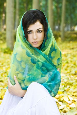 Woman covered by headscarf in a forest. photo