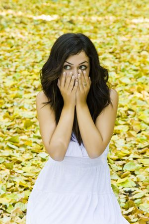 Young surprised woman surrounded by fallen leaves. Stock Photo - 3511867