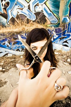 Young goth styled woman holding scissors for... photo