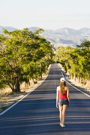 teen legs: Young woman walking in the middle of the road.