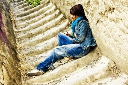 Young thoughtful woman sitting on stone stairs. Stock Photo - 3538156