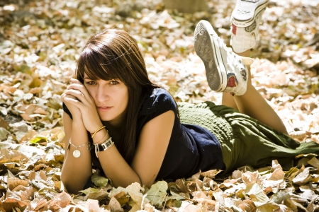 woman laying: Young woman laying over fallen leaves. Stock Photo
