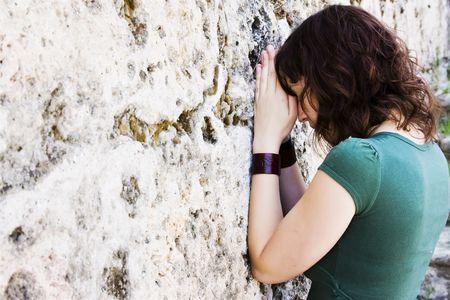 almighty: Giovane donna di preghiera contro la parete di pietra.
