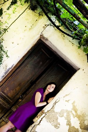 Disturbed young woman over cracked old wall. photo