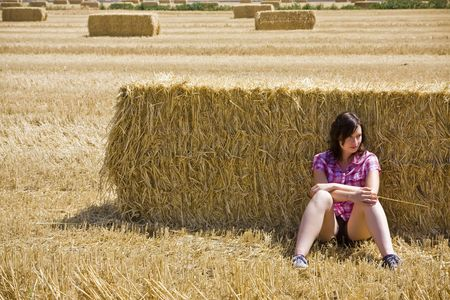 Young farmer resting on the haystack photo