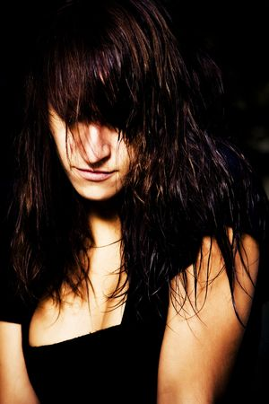 tormented: Serious woman portrait with hair covering her eyes. Stock Photo