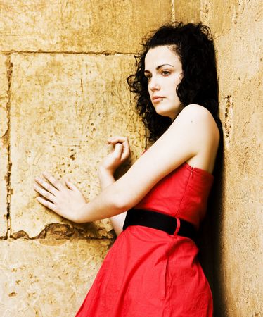 Young sad woman against stone wall. photo