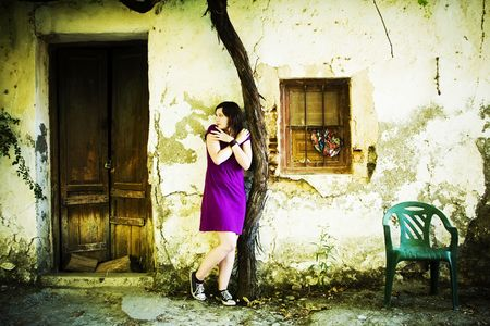 Young scared woman in old cracked wall. photo