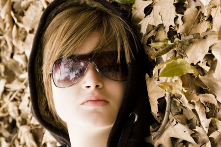 Young fashion woman surrounded by autumn leaves photo