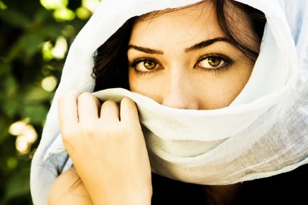 middle eastern clothing: Young green eyed woman behind veil.
