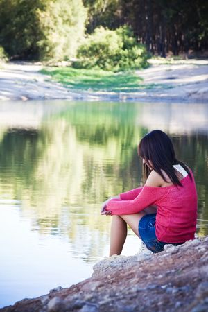 Thoughtful woman sitting in lake shore. Stock Photo