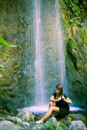 exposed: Woman brushing her wet hair under long exposed waterfall