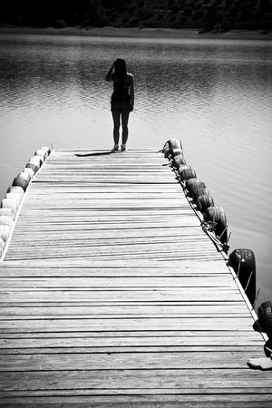 pontoon: Silhouetted woman and the end of a pier over the lake. Stock Photo