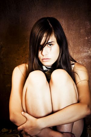 Young scared woman over grunge background photo