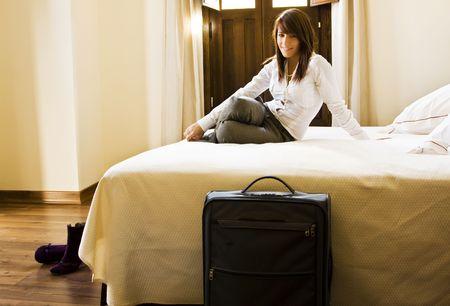 viajero: Empresaria de pelo largo descanso en la cama.