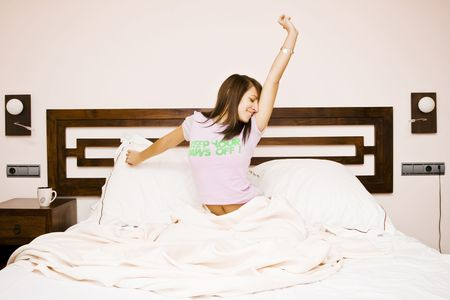 Young beautiful woman waking up in the morning photo