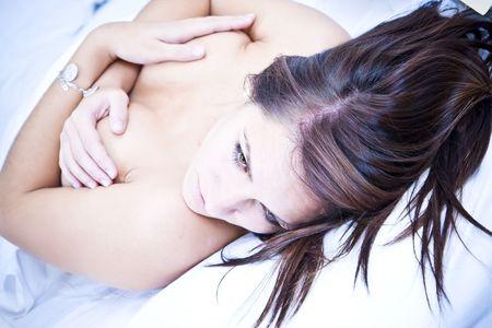 Sensual young woman laying  in white sheet. Stock Photo - 3676672