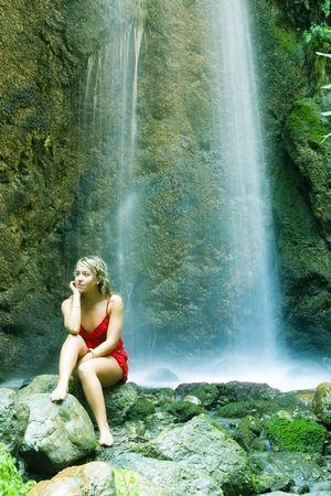 Blond young pensive woman under long exposed waterfall Stock Photo - 3676674