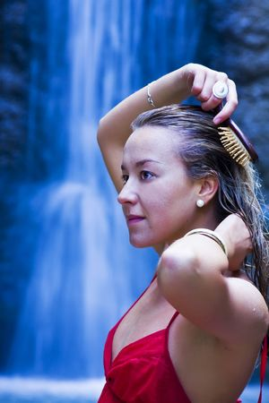 Young blond woman brushing her hair, long exposed cascade as background Stock Photo - 3676668