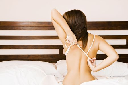 Young beautiful woman undressing in bed. Stock Photo