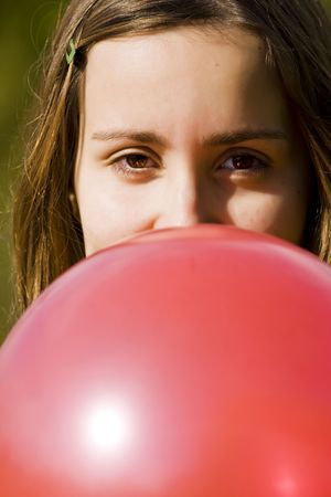 Young woman inflating red balloon, vertical composition photo