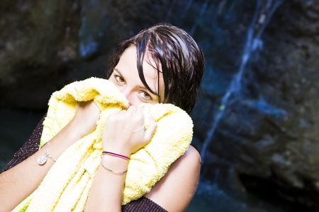 Young beautiful woman using towel over natural waterfall background photo