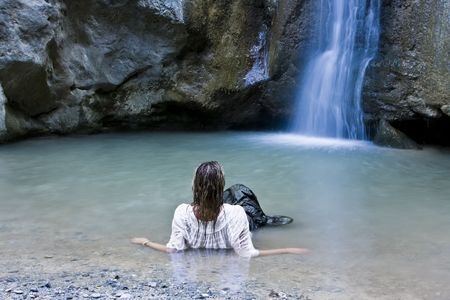 long lake: Young blond woman swimming in waterfall lake. Stock Photo