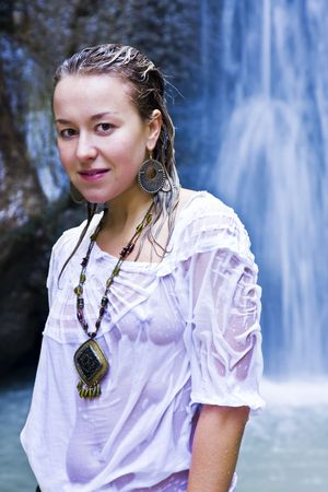 transparent dress: Young woman smiling at camera with blue waterfall as background