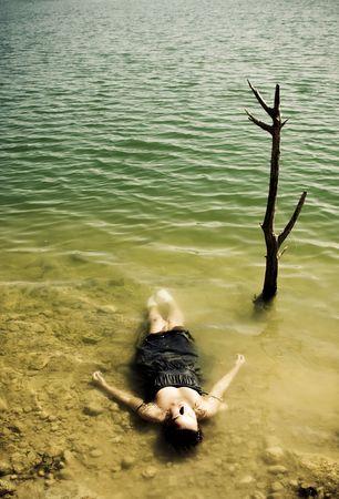 vermoord: Jonge vrouw lichaam over meer water, gesloten ogen.
