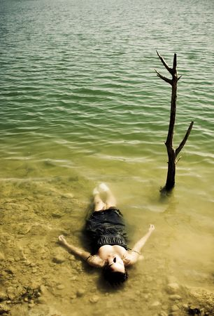 riverside tree: Young woman body over lake waters, closed eyes.