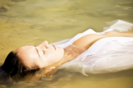 Sensual woman in water wearing white shirt photo