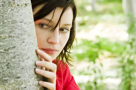 Young beautiful woman playing hide and seek in the trees. photo