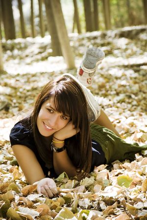 Young woman laying over fallen leaves. photo