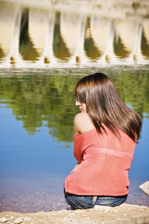 Thoughtful woman sitting in lake shore. photo