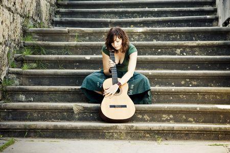 Young beautiful music performer caressing her guitar photo