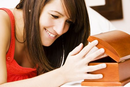 Smiling woman in bed opening a gift. photo
