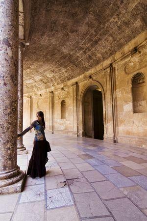 pillar: Young beautiful woman posing in ancient corridor