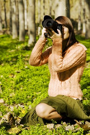 Young pretty female photographer in a forest. photo